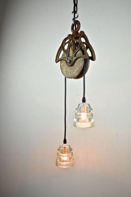 Foto de duas lâmpadas, cada uma de uma lado de uma roldana pendurada no teto.