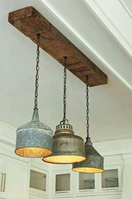 Foto de três lâmpadas ligadas a uma madeira pendurada no teto por uma corrente. as lâmpadas estão dentro de recipientes metálicos grandes e largos.