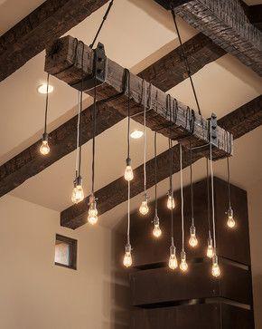 Foto de diversas lâmpadas penduradas em um tronco de madeira suspenso no teto.
