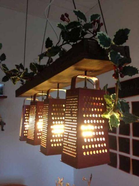 Foto de quatro lâmpadas enfileiradas penduradas em uma madeira suspensa no teto com pequenas folhas sobre ela. As lâmpadas estão dentro de raladores de queijo.