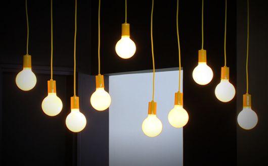 Foto de lâmpadas penduradas no teto, algumas mais altas e outras mais baixas.