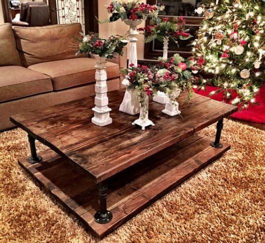 Mesa de centro com base e tampo de madeira em uma tapete da sala de estar. Ela é decorada com vasos de flores em sua superfície e está próxima a uma árvore de natal.