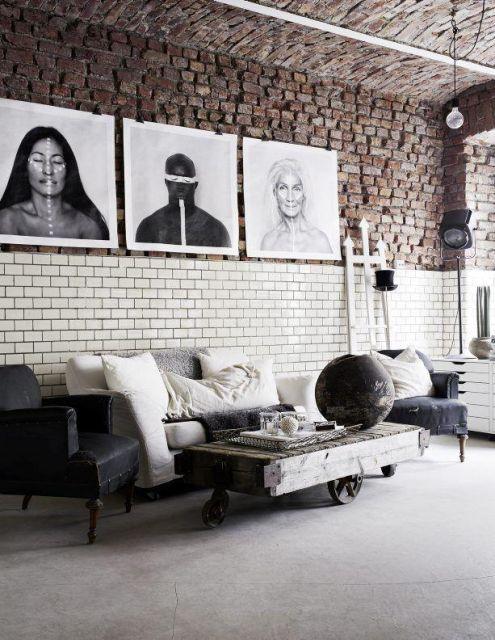Foto de um loft com decoração industrial. Em frente ao sofá está uma mesa de centro quadrangular com rodinhas e feita de madeira.