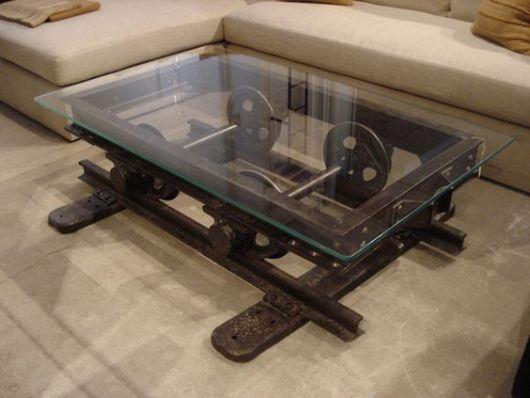 Foto de uma mesa de centro quadrangular baixa feita toda com ferro e engrenagens e seu tampo feito de vidro.