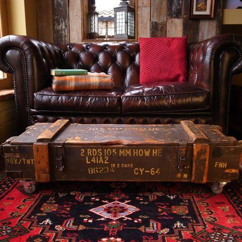 Foto de uma mesa de centro quadrangular baixa posicionada em frente a um sofá. A mesa parece um baú antigo com rodinhas.