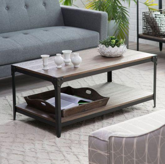 Foto de mesa de centro quadrangular com dois níveis feitos com tampos de madeira posicionada entre dois sofás.