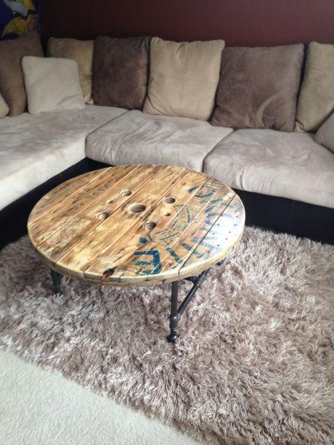 Foto de uma mesa de centro industrial redonda com tampo de madeira e sustentação feita a partir de canos.