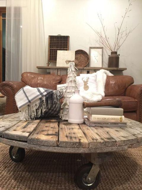 Foto de uma mesa de centro industrial redonda baixa posicionada em frente a um sofá. Seu tampo é feita de madeira e ela tem três rodinhas como sustentação.