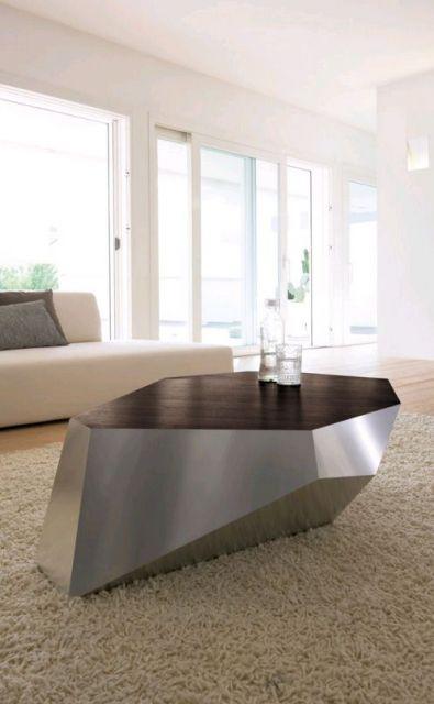 Foto de uma mesa de centro metálica cujo formato se dá através de formas geométricas distintas. Ela está posicionada no centro de uma sala de estar ampla com grandes portas e janelas.