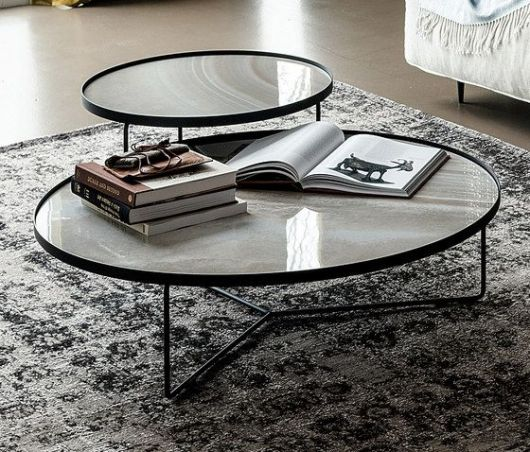 Foto de mesa de centro industrial redonda com dois tampos, um grande e baixo e outro pequeno e alto.