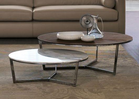 Foto de mesa de centro industrial redonda posicionada em frente a um sofá em piso de madeira. Ela tem dois níveis diferentes, um com tampo grande e alto e outro pequeno e baixo.