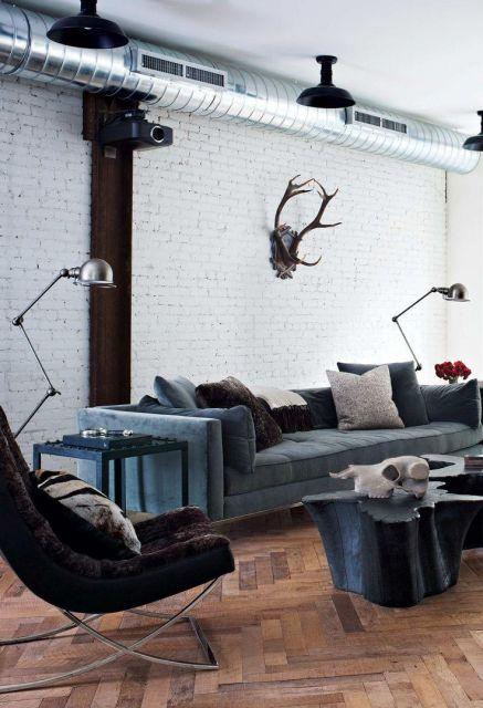 Foto de um lounge industrial com paredes de tijolos expostos e uma mesa industrial posicionada no chão de madeira. A mesa é feita a partir de um tronco com formas sinuosas e tem um crânio de animal posicionado sobre ela.