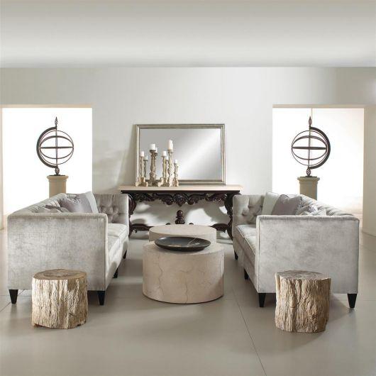 Foto de um ambiente composto por uma bancada com espelho, dois sofás e duas mesas de centro redondas, além de objetos de decoração de arte. As mesas estão posicionadas entre os dois sofás e tem sua altura no mesmo nível do assento do sofá.