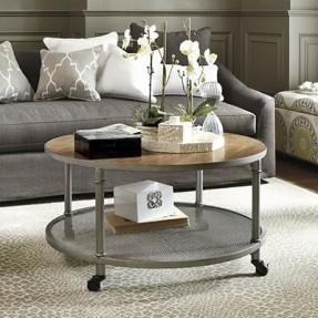 Foto de mesa de centro industrial redonda com dois níveis, um com tampo de madeira e outro com tampo de vidro. Ela está posicionada entre os sofás de um ambiente e tem rodinhas como sustentação.
