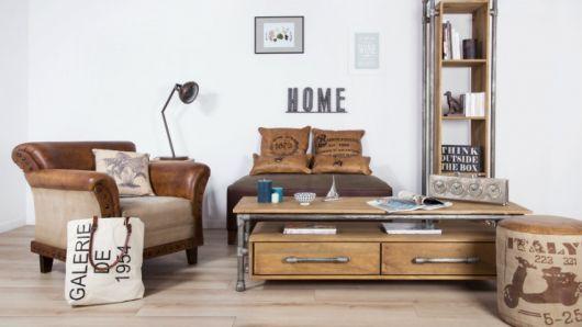 Foto de um ambiente com dois puffs e uma poltrona. Entre eles está uma mesa de centro quadrangular feita de madeira com duas gavetas em sua parte inferior.