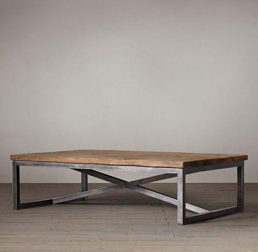 Foto de uma mesa de centro quadrangular com base de metal e tampo de madeira.