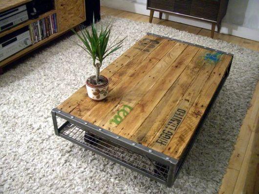Foto de mesa de centro quadrangular em uma tapete com sua base feita de metal e o tampo de madeira. Acima dela está um pequeno vaso de planta.