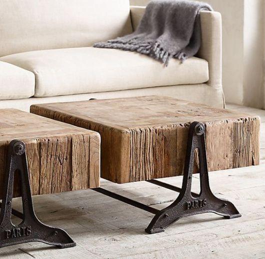 Foto de mesa de centro com a base feita de metal rústico e o tampo com um bloco grosso de madeira.