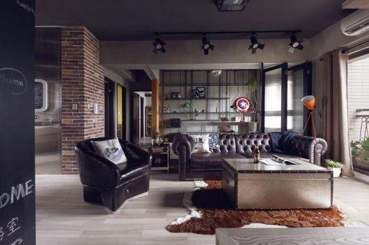 Foto de um loft com decoração industrial. Entre o sofá e a poltrona está uma mesa de centro quadrada alta que parece uma caixa de metal.
