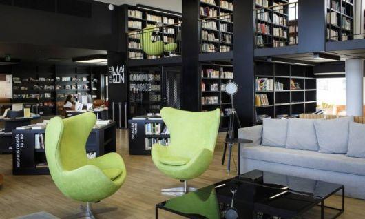 Modelo de poltrona verde em sala com biblioteca preta.