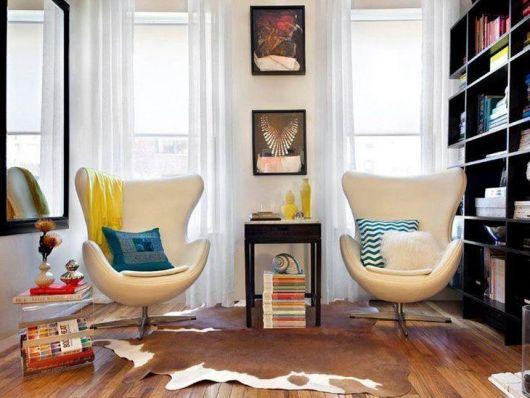 Sala clean com piso de madeira e poltronas bege claro.
