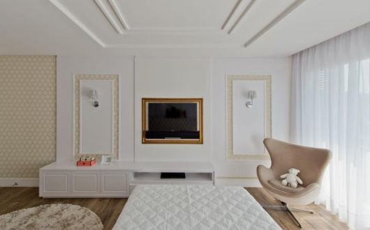 Modelo de sala branca com poltrona cor nude.