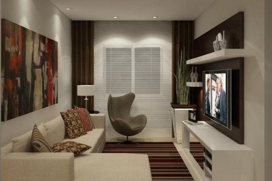 Sala branca com cortinas marrons e parede branca com poltrona bege escuro.