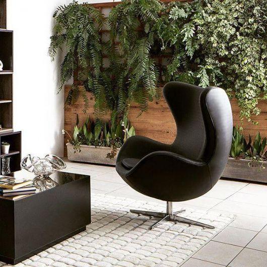 Sala de estar com tapete branco, mesa de centro preta e poltrona na mesma cor.