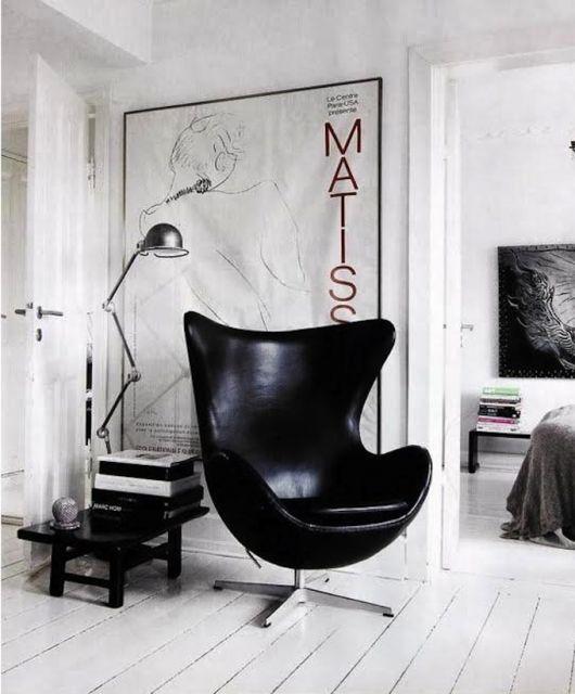 Sala branca com luminária de chão e poltrona egg preta.