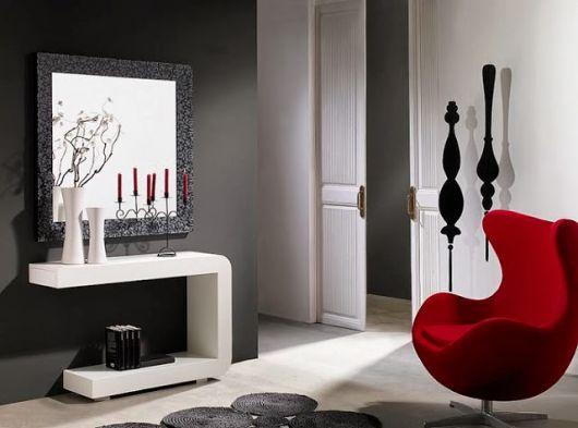 Sala cinza com branco, móveis brancos e poltrona capitonê.