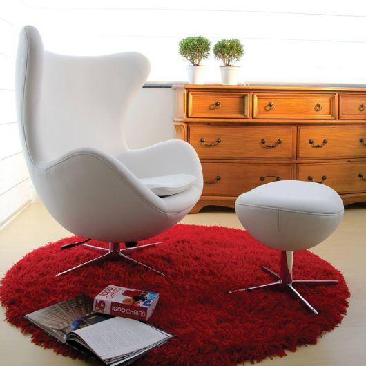 Poltrona branca com puf localizada em cima de tapete felpudo vermelho.