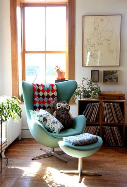 Sala com poltrona verde claro e paredes brancas em madeira.