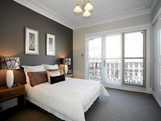 Foto de um quarto com cama de casal cheia de almofadas, uma cabeceira do lado e uma saída para sacada. O carpete é escuro e não tem detalhes.