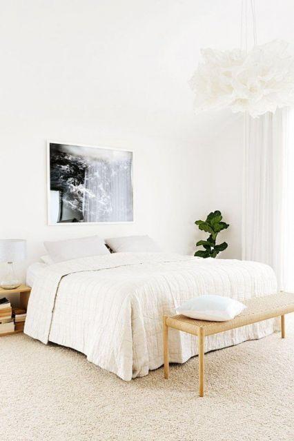 Foto de um quarto todo decorado com tons claros e um carpete em tom pastel.