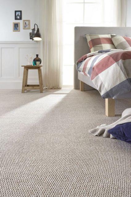 Foto de um carpete levemente detalhado em um quarto com uma grande janela ao fundo que traz muita iluminação natural.