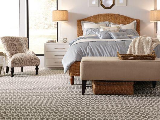 Foto de um quarto com carpete feito a partir da contraposição de tons claros e escuros. Ele é decorado com pequenos círculos desenhados ao longo de toda a sua extensão.