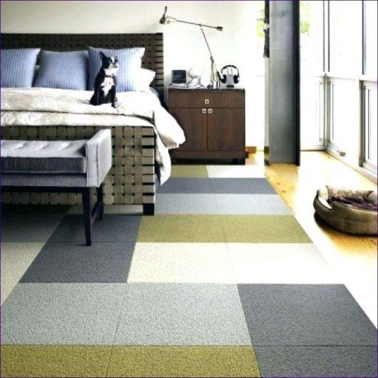 Foto do carpete em um quarto de adulto. O carpete não cobre toda a extensão do piso.  Ele é colorido e instalado a partir de placas, com cores revesadas entre uma e outra.