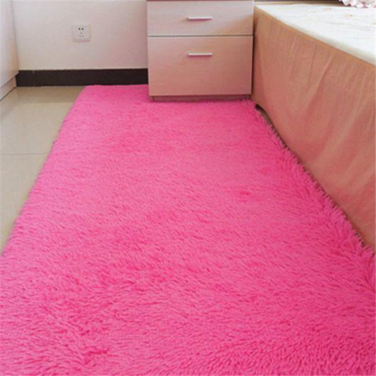 Foto de um carpete rosa pink posicionado ao lado da cama bem fofo.