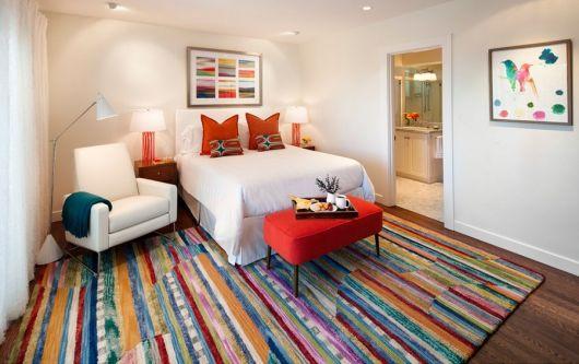 Foto de um carpete em um quarto com suíte. Ele não cobre toda a extensão do piso, deixando algumas partes de madeira à mostra. O carpete é feito com diversos tons diferentes por meio de tiras coloridas.