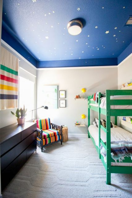 Quarto de criança com decoração espacial onde há uma beliche e uma pequena poltrona colorida. No chão há um carpete claro com pequenos detalhes formados a partir de formas geométricas.