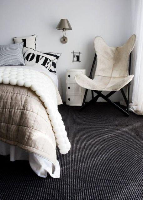 Foto de um quarto onde vemos parte de uma cama e uma poltrona. O carpete é escuro.