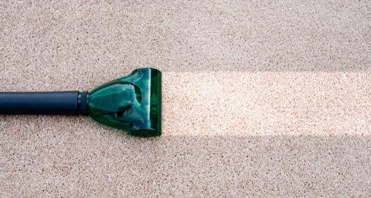 Foto de um aspirados limpando um carpete. Ele deixa um rastro de limpeza.