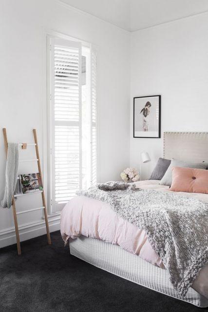 Foto de um quarto com uma cama de casal grande e uma janela ampla, bem iluminada. O carpete é escuro e parece ser bem fofo.