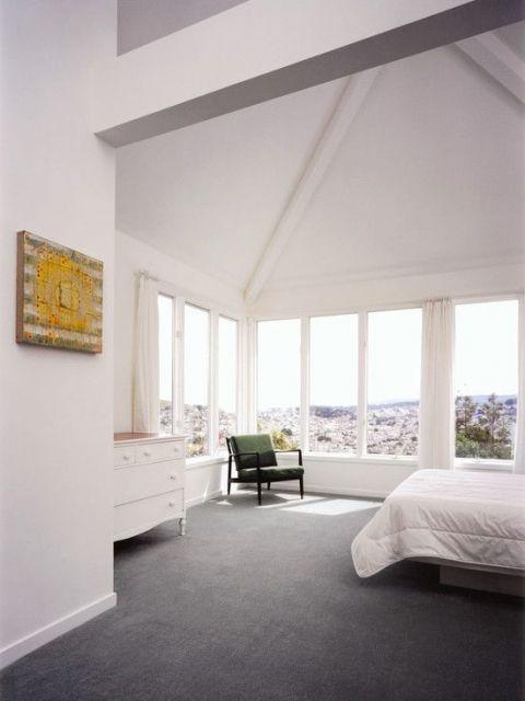 Foto de um quarto amplo com grandes janelas em duas das quatro paredes. O carpete é escuro e está sendo levemente iluminado pela luz que entra das janelas.