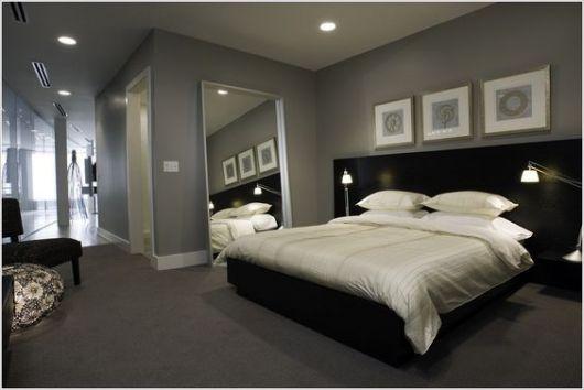Foto de um quarto com cama de casal que tem acesso direto a uma corredor. O carpete é escuro e combina com os tons escuros da parede e da cama.