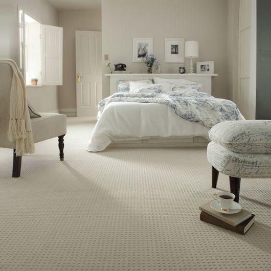 Foro de um quarto com carpete claro onde todo o resto também é claro, como as paredes, os móveis e a cama.