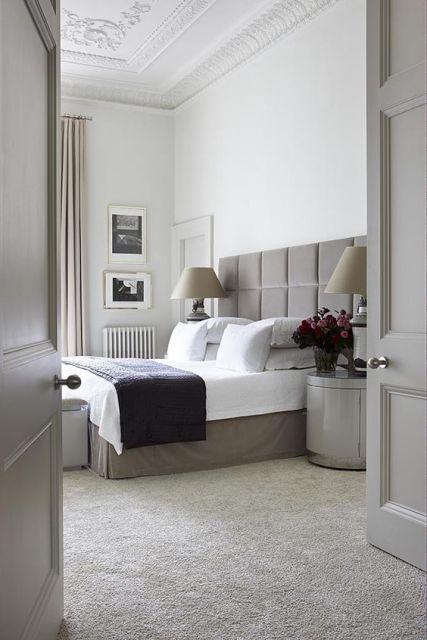 Foto de um quarto com cama de casal e portas grandes. O carpete é claro e combina com toda a mobília.