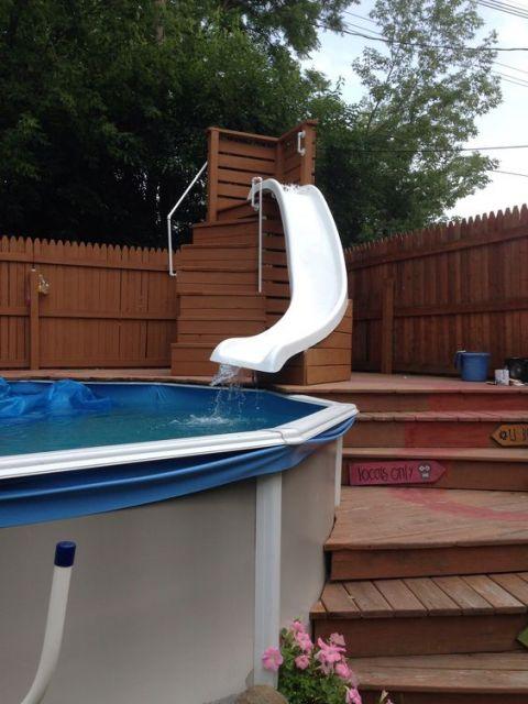 Escorregador para piscina de fibra no canto de uma piscina levemente sinuoso com uma escada de madeira ao seu lado.