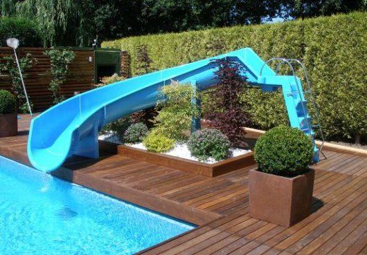Escorregador para piscina de fibra baixo e extenso que passa por cima de um pequeno jardim e vai até a água.