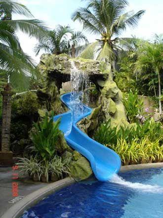 Escorregador para piscina de fibra grande no apoiado em pedras que passa por dentro de uma cascata.